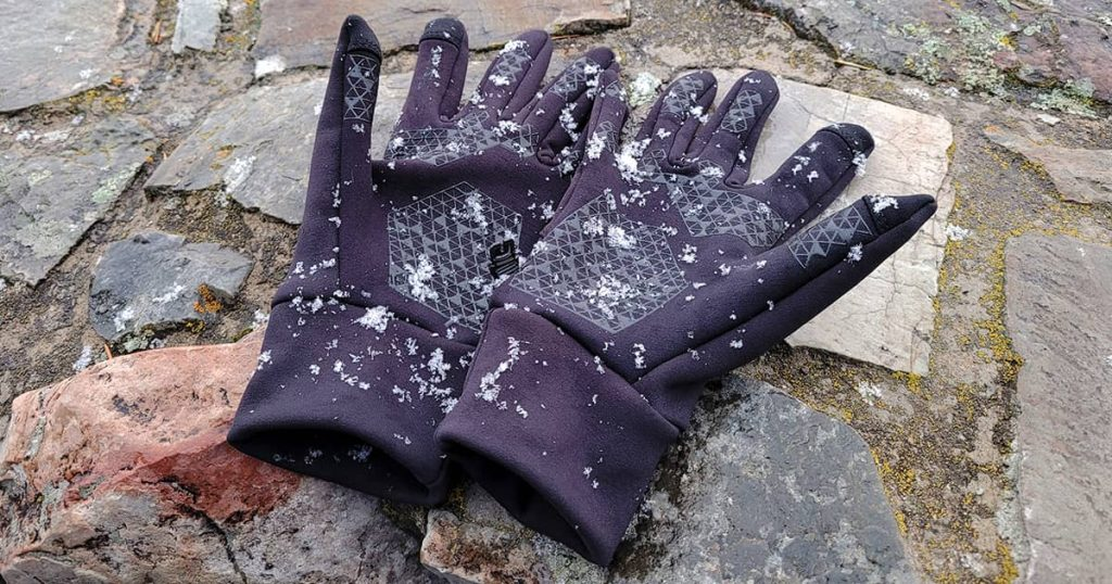 A pair of black gloves laying on brick wall with snow falling and trees in the background