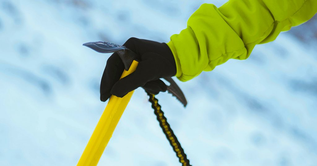 Hicking gloves and Yellow ice axe in the snow