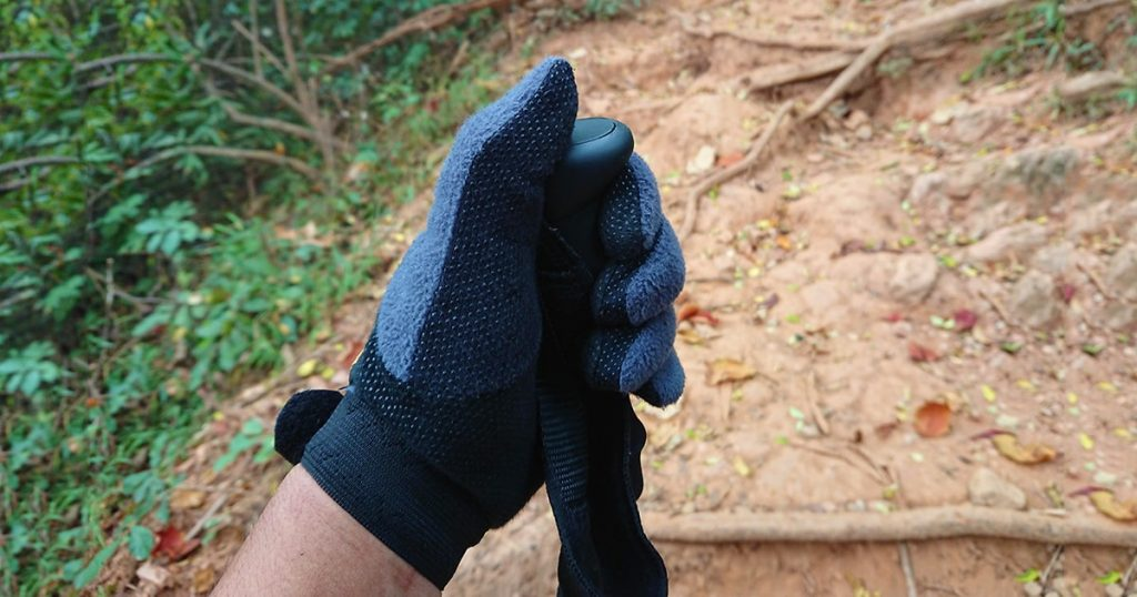 hand with glove catch the trekking pole on walk way in deep forest