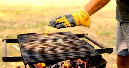Man hand in glove check barbecue temperature for grilling