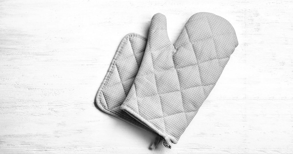 Oven glove and potholder on white wooden background, flat lay