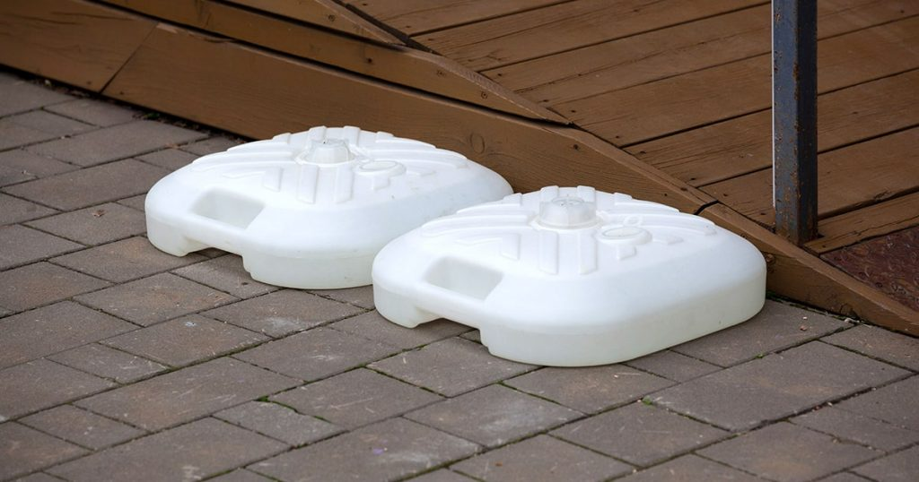 two plastic white bases of the beach umbrella stand are lying on the road