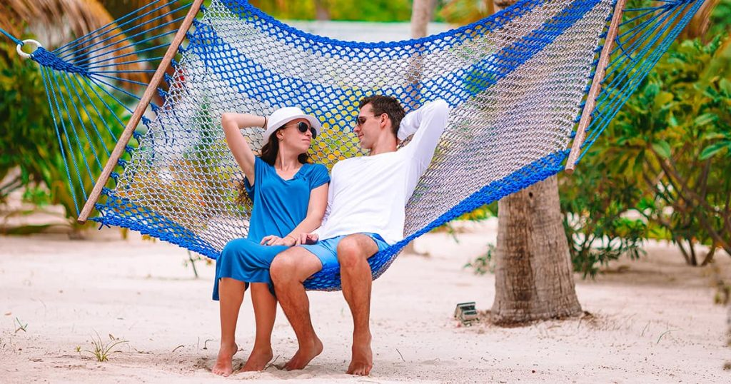 Family relaxing in hammock on the beach vacation