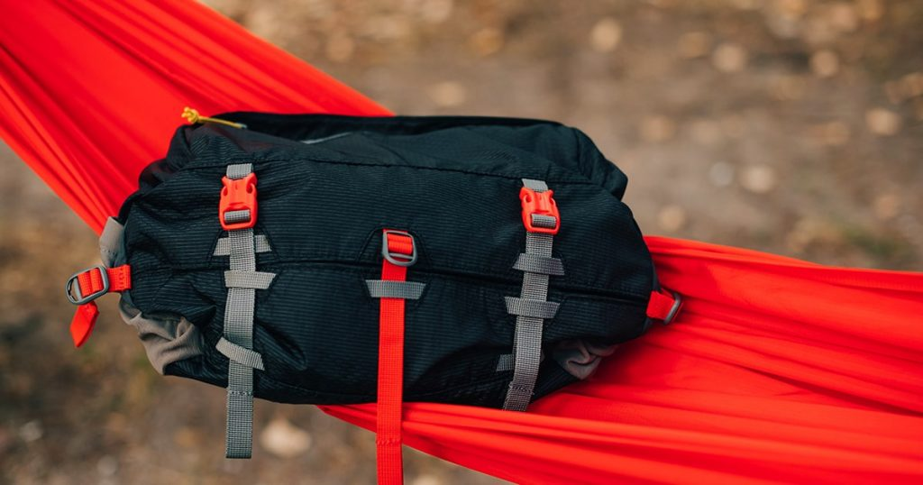 Travel waist bag lies on a red hammock in the woods
