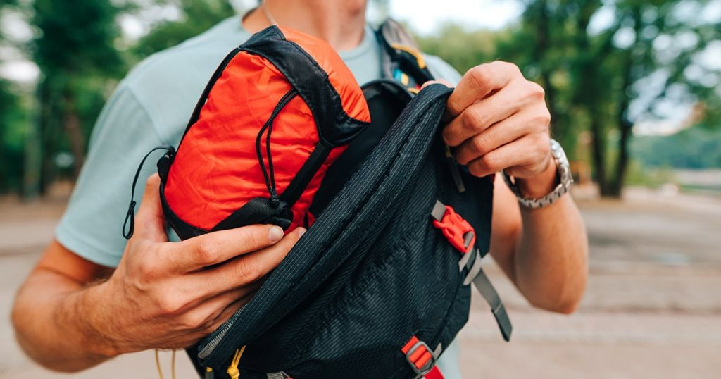 tourist puts a red bag with travel gear in a waist bag which he carries on his shoulder