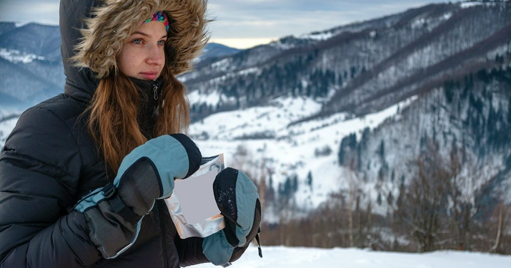 woman hiking outdoors with gloves and hat,