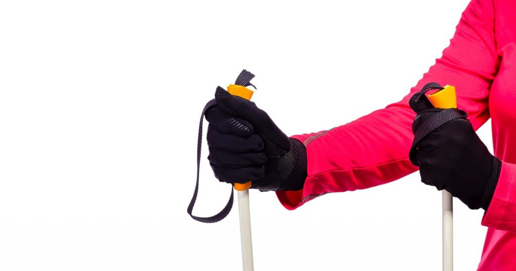 Closeup of Female Hands in Protective Gloves Holding Nordic Walking Sticks