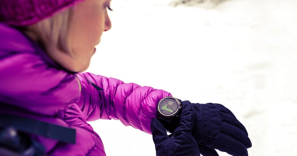 Woman hiker checking the elevation on sports watch, smartwatch with altimeter app in winter woods and mountains