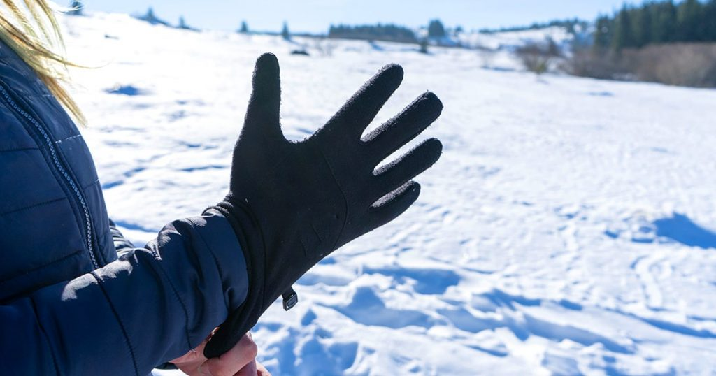 Woman putting winter sport glove in hand, getting ready for extreme cold weather