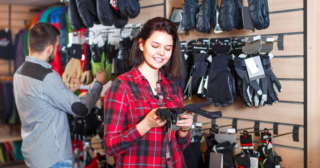 Young girl with a man choose new protective gloves in a sports goods store