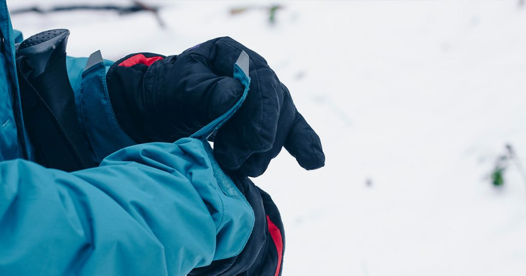 Hiker's hands in gloves are adjusting membrane jacket in the winter forest
