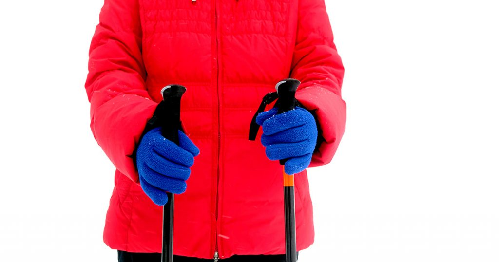 Woman in red sport jacket and blue gloves holds two sticks for hiking in winter