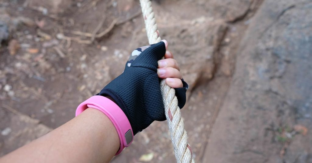 close up women climbing the mountain in hiking gloves