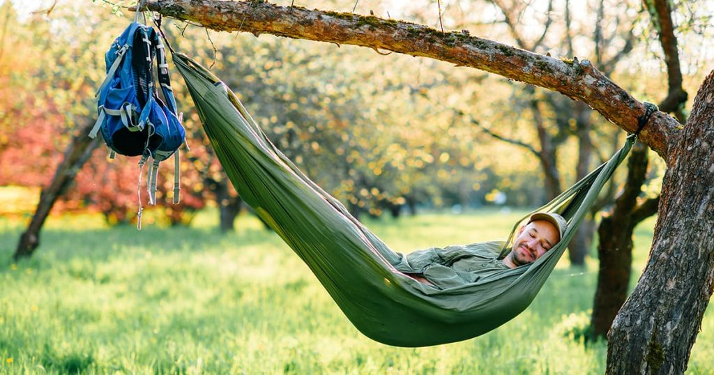 man in green hat lying in hammock on apple tree at blooming garden in summer sunny day on vacation